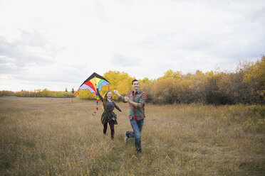 Couple flying a kite in autumn field - HEROF33290