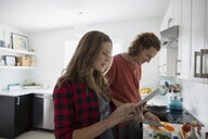 Couple with digital tablet cooking in kitchen - HEROF33314