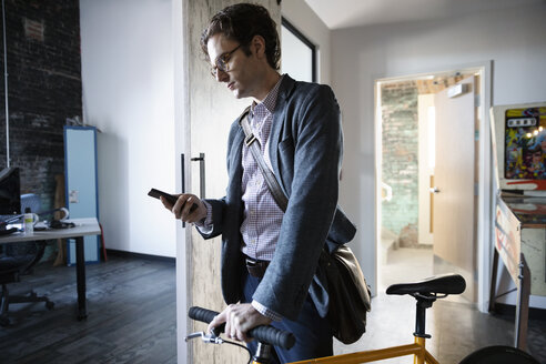 Creative businessman with smart phone walking bicycle in office - HEROF33347