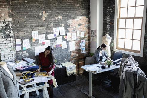 Female fashion designers working in loft office - HEROF33494