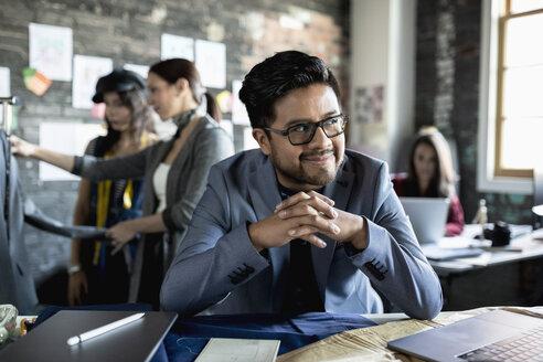 Confident male fashion designer working in office - HEROF33530