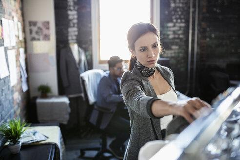 Female fashion designer browsing clothing on rack in office - HEROF33533