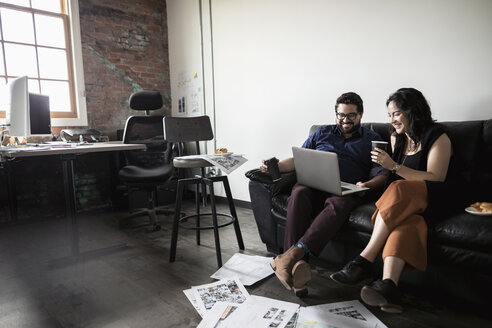 Creative business people drinking coffee and using laptop on office sofa - HEROF33557