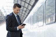Businessman using cell phone on station platform - DIGF06421