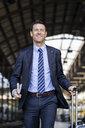 Smiling businessman walking with suitcase on station platform - DIGF06427