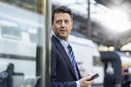 Businessman with cell phone at train station - DIGF06430