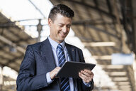 Smiling businessman using tablet at train station - DIGF06442