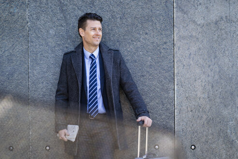 Smiling businessman with suitcase standing at a wall - DIGF06457