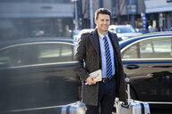 Businessman with suitcase at the street in the city - DIGF06463