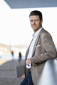 Smiling businessman with tablet standing outdoors - DIGF06481