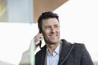 Portrait of smiling businessman on cell phone outdoors - DIGF06487