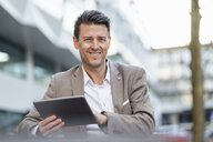 Portrait of smiling businessman using tablet outdoors - DIGF06496