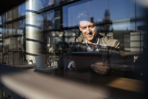 Businessman using tablet behind the window in a cafe - DIGF06499