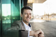 Portrait of smiling businessman outside a building in the city - DIGF06511