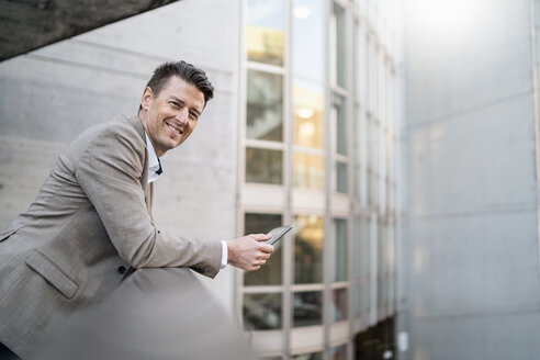 Portrait of smiling businessman with tablet leaning on railing - DIGF06514