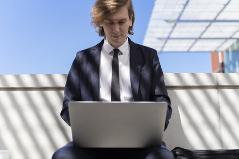 Italy, Florence, young businessman using laptop outdoor - FMOF00510