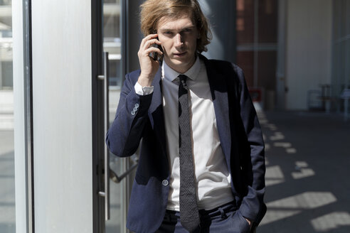 Italy, Florence, young businessman on smartphone outdoor - FMOF00513