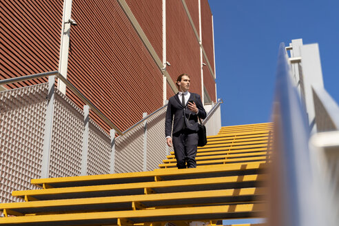 Italy, Florence, young businessman with earbuds and smartphone on stairs - FMOF00531
