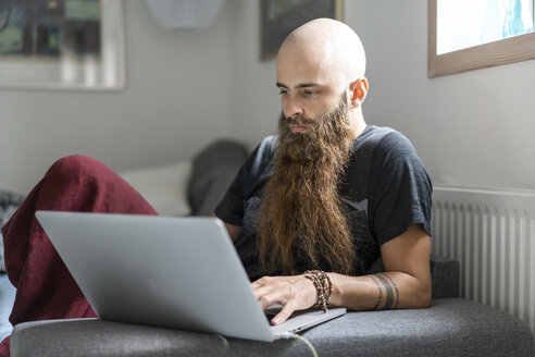 Portrait of hipster using laptop at home - AFVF02714
