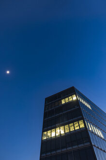 Germany, Stuttgart, lighted windows at modern office building at blue hour - WDF05214