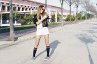 Spain, smiling teenage girl using smartphone on a road - ERRF00830