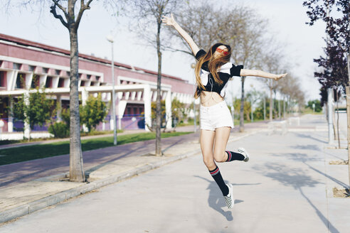 Spain, happy teenage girl jumping on a road - ERRF00833