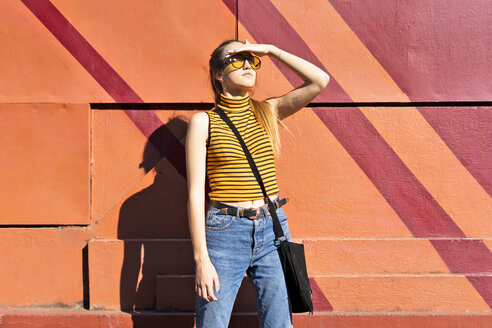 Teenage girl at a wall enyoying the sunshine - ERRF00854