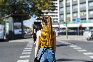 Spain, back view of a teenage girl on the street in summer - ERRF00857
