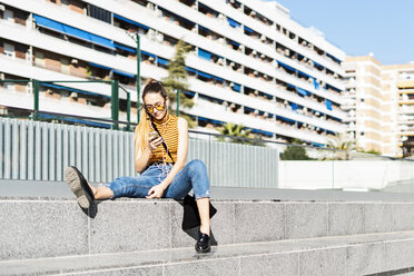 Spain, teenage girl with smartphone and earphones sitting on stairs in the city - ERRF00860