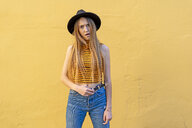 Portrait of annoyed teenage girl wearing hat at yellow wall - ERRF00884