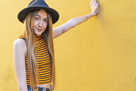 Portrait of teenage girl wearing hat at yellow wall - ERRF00887
