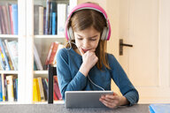 Little girl doing homework with headphones and digital tablet - LVF07945