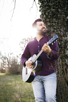 Man playing guitar at a tree on a meadow - HMEF00266