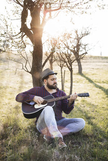 Man playing guitar at a tree on a meadow - HMEF00275