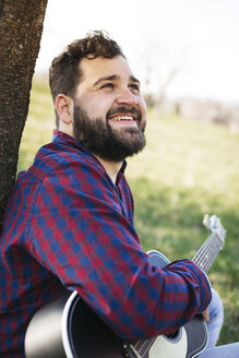 Portrait of smiling man with guitar at a tree on a meadow - HMEF00278