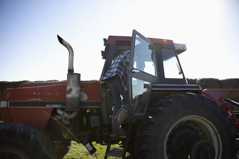 Male farmer climbing into tractor on sunny farm - HEROF33596