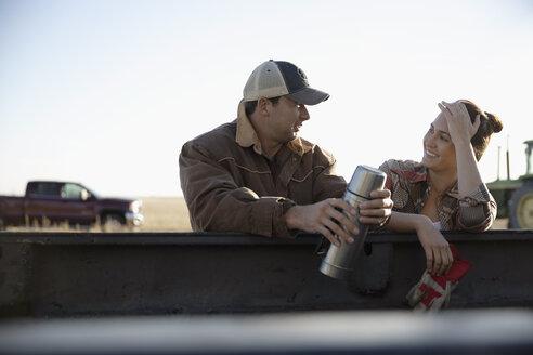 Farmer couple drinking coffee, taking a break on farm - HEROF33644