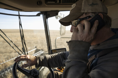 Male farmer talking on smart phone and driving tractor - HEROF33659