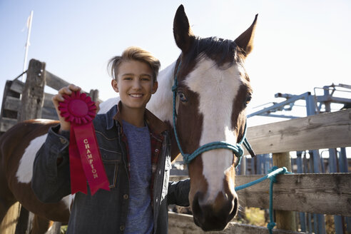 Portrait confident boy with horse holding red champion ribbon - HEROF33692