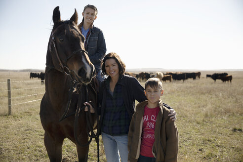 Portrait smiling woman and boys with horse on sunny ranch - HEROF33698