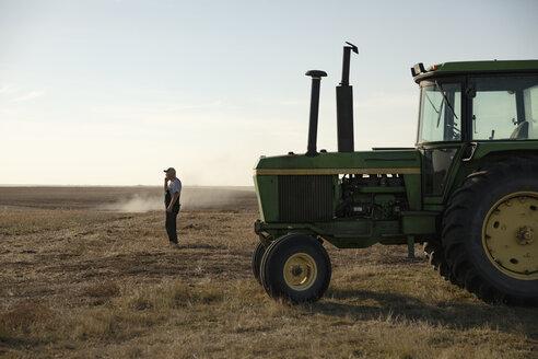 Male farmer standing near tractor in sunny field - HEROF33719
