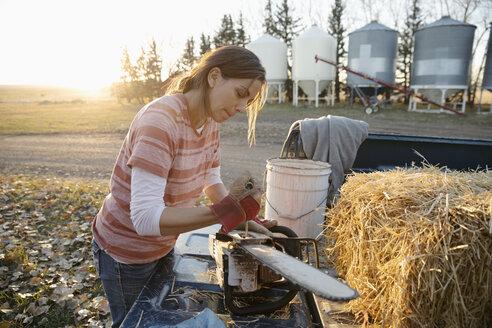 Female farmer fixing chainsaw on farm - HEROF33731