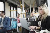 Businesswoman using laptop on bus - HEROF33746