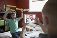 Boy photographing brother holding trophy with digital tablet - HEROF33782