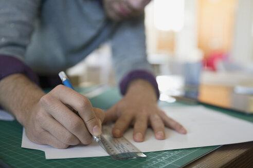 Close up of designer using ruler and bradawl on cutting mat - HEROF33791