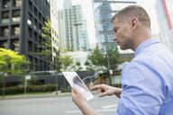 Businessman using digital tablet on city street - HEROF33887