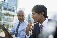 Businessman talking and using digital tablet - HEROF33911