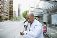 Businessman checking the time on wristwatch at city bus stop - HEROF33920