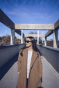 Young woman wearing coat and sunglasses standing on a bridge - RSGF00168