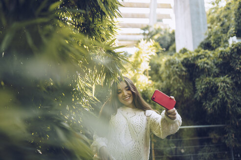 Happy young woman taking a selfie in a park - RSGF00183